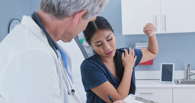 Japanese woman explaining shoulder pain to doctor in exam room. Patient with rotator cuff injury talking to medical professional