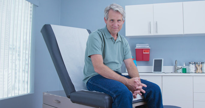 Portrait of Senior Caucasian male patient sitting on exam room table in clinic looking at camera. Older man in hospital for regular check up