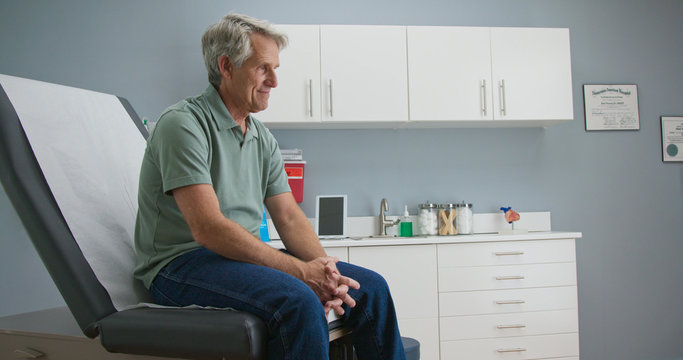 Senior Caucasian male patient waiting patiently for doctor while sitting on exam room table. Older man going to regular appointment for annual check up