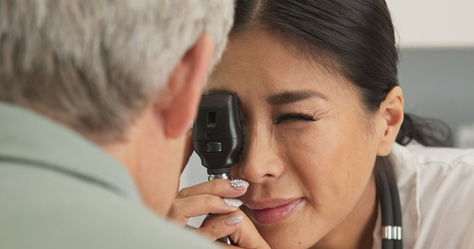 Close up on doctor using ophthalmoscope to look into eyes of senior male patient. Japanese woman primary care physician or ophthalmologist doing check up