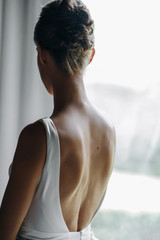 Bride's morning portrait. Bride dressed like a balerina stands before a bright window