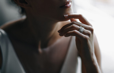 Bride's tender fingers touch her chin