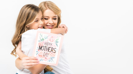 adorable child hugging smiling mother with happy mothers day greeting card in hand on white background