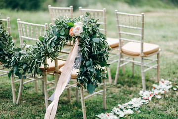 Floral garlands of green eucalyptus and pink flowers decorate wedding arch and chairs on the hill