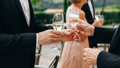 Two man clang glasses with champagne standing in the hall during a reception