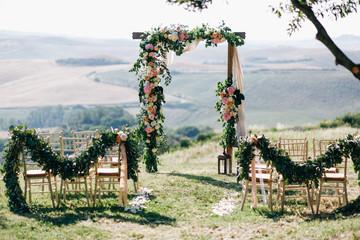 Italian wedding decoration. Green eucalyptus, oranges and pink flowers decorate wedding altar