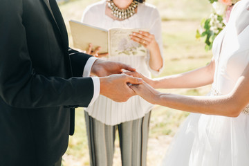 Bride and groom hold their hands together during the ceremony
