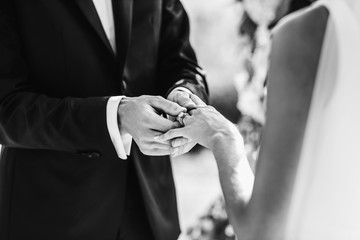Groom puts wedding ring on bride's finger. No face