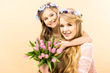 beautiful woman and adorable daughter holding bouquet of pink tulips and looking at camera on yellow background