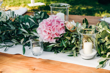 Floral garland of eucalyptus lies on the wedding dinner table
