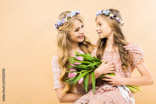 smiling daughter with bouquet of pink tulips sitting on mothers knees on yellow background