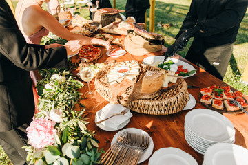 People take delicous salty snacks from the table arranged in Italian style
