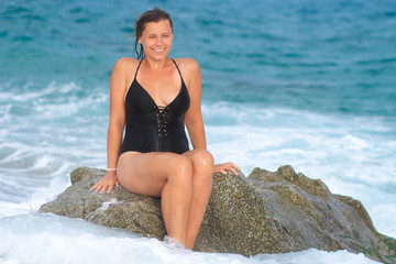 Wet woman in swimsuit sitting on rock on sea beach during bathing.
