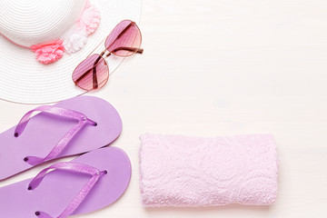 Beach accessories on a white background - sunglasses, towel, slippers and hat. summer comes concept