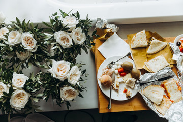 Bouquets of flowers stand in the vases by the table with snacks