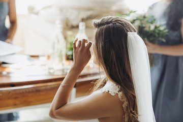 Look from behind at charming bride touching her eyes