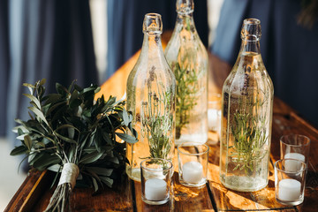 Table decor. Bottles with greenery and glasses with candles stand on the table with wedding bouquet on it