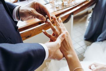 Wedding ceremony. Groom puts ring on bride's finger