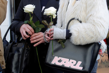 People hold white roses as they stand outside the Chanel fashion boutique after news that German haute-couture designer Karl Lagerfeld, artistic director at Chanel and an icon of the global fashion industry for over half a century, has died, aged 85, in Pa