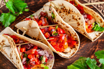Concept of Mexican cuisine. Mexican appetizer Tacos with vegetables, beans, paprika, chilli peppers on fried unleavened bread cakes. Taco for veterinarians. Background image.
