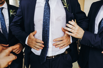 Old man in classy suit holds his hands on the chest. No face