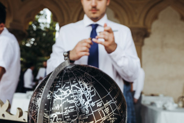 Man in the suit stands before the black globe with silver letterings