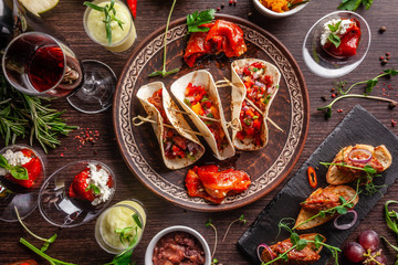 The concept of Mexican cuisine. Mexican food and snacks on a wooden table. Taco, sorbet, tartar, glass and bottle of red wine. Background image. Top view, copy space