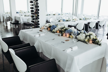 Wedding table decoration. Floral garland of greenery and blue flowers lies between glasses on the white table