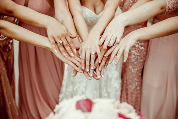 Bride and bridesmaids in pink dresses rich out their hands with rings on fingers