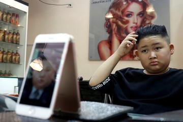 To Gia Huy, 9, has a haircut in a North Korean leader Kim Jong Un style in a haircut salon in Hanoi