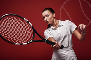 Game, Set, Match Young tennis player standing isolated over red background with a racket and a ball