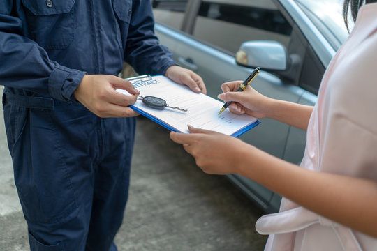 Technicisn repairman giving car key to woman in workshop.Workshop mechanic repair client car in auto service shop..female customer sign paper insurance bill contact in garage. Fixing car concept.