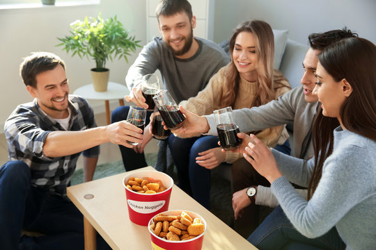 Group of friends eating nuggets and drinking soda at home