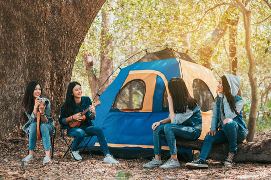Friends Group of Young Asian women camping and resting at forest playing ukulele,take a photo happy on weekend.