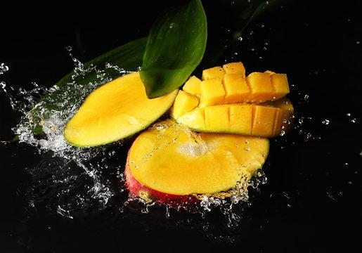 Ripe cut mango with water splash on dark background