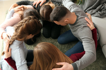 Group of people praying together indoors Wall mural