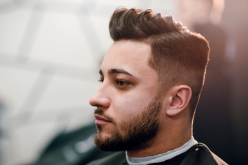 Side portrait of young attractive brunette man at the barbershop. Man getting haircut by hairdresser in barbershop.