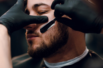 Young brunette man is getting shaved with a vintage razor by a hairdresser at the barbershop. Beard haircut. Close up