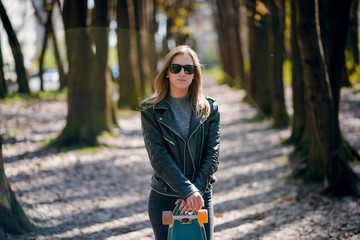 Portrait of young beautiful woman in stylish outfit walking with longboard in the autumn park. Sunny day
