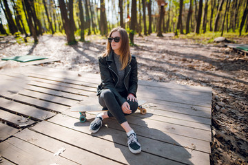 Young beautiful hipster girl in stylish outfit with black sunglasses sitting on the longboard in the autumn park, forest on sunny day.