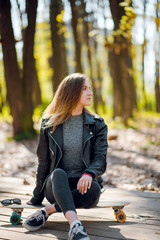 Young hipster woman in stylish outfit sitting on the longboard in the autumn park, forest on sunny day.
