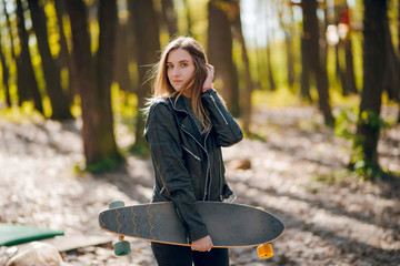 Young hipster woman in stylish outfit walking with the longboard in the autumn park, forest on sunny day.