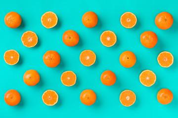 Fruit pattern of fresh mandarin slices on blue background. Flat lay, top view. Pop art design, creative summer concept. Half of citrus in minimal style. Tangerine.. Creative layout.