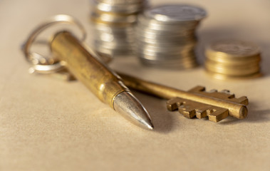 money coins, bullet and key on a wooden table- the topic of business and war