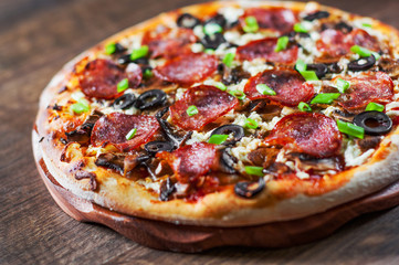 Pizza with Mozzarella cheese, salami, pepper, pepperoni, olives, Spices and mushroom. Italian pizza on wooden table background