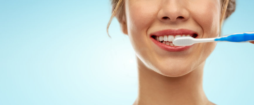 oral care, dental hygiene and people concept - close up of smiling woman with toothbrush cleaning teeth over blue background