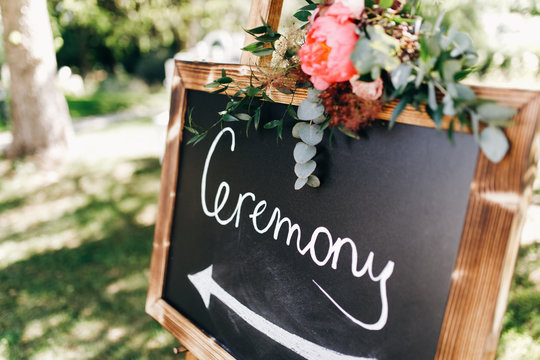Black board with lettering 'Ceremony' stands on the path in the garden