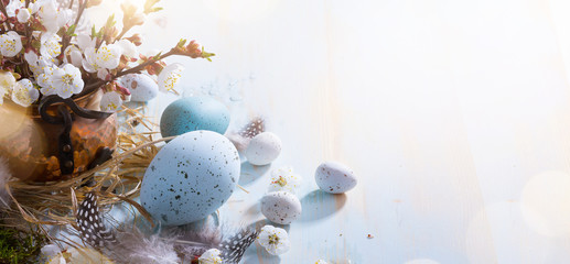 bright Easter background;  Easter eggs basket and sprig flowers on blue table background