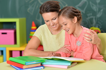Portrait of little girl with her mother doing homework