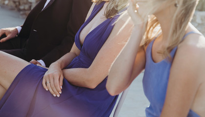 Women in light evening dresses sit on the chairs during the ceremony